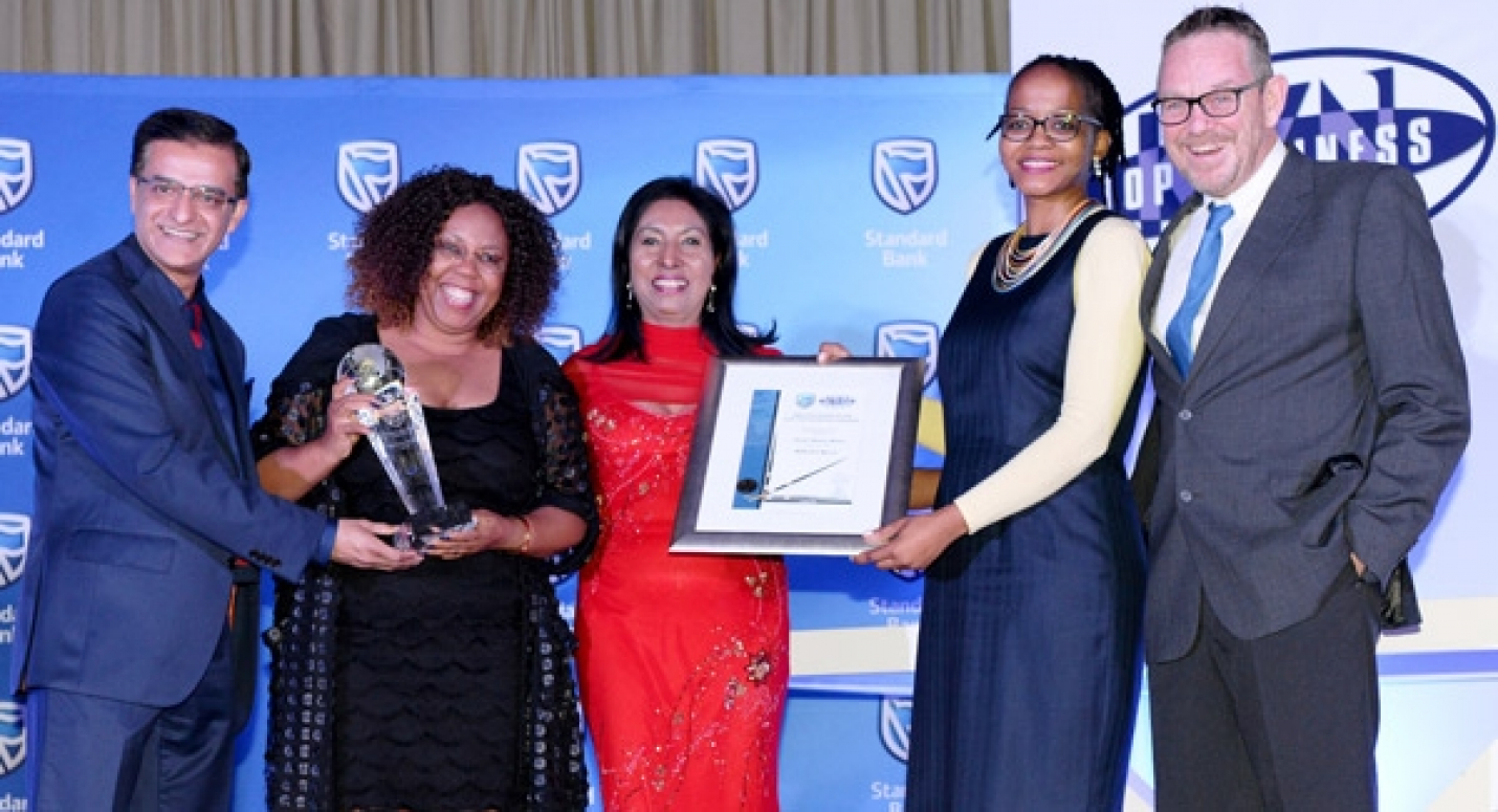 Winning smiles (L-R): Imraan Noorbhai, Standard Bank KZN Provincial Head hands Stella Khumalo,  the CEO uShaka Marine World her winning trophy while Lalita Dhasiar-Ventura (KZN Top Business) and Mpume Mabuza, the marketing director at uShaka Marine World holding their winning certificate; Grant Adlam (KZN Top Business)